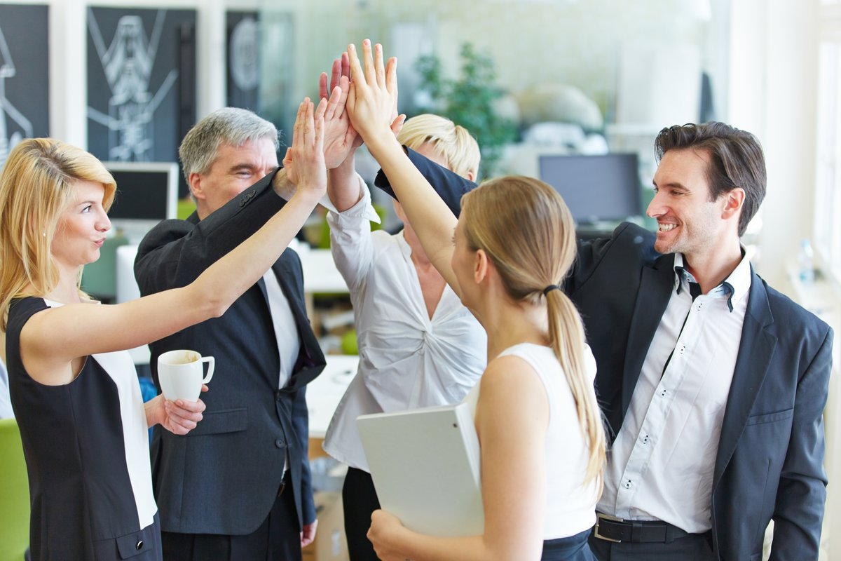 Glückliches Business Team macht High Five mit den Händen im Büro