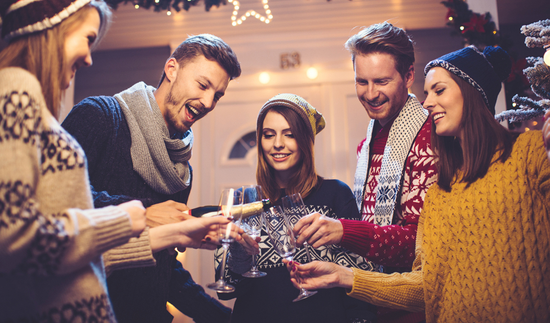 Young group of friends having fun outdoors in front of house. Pouring champagne in glasses. Wearing knitted sweaters, hats and scarfs. House, yard and tree are decorated with festive string lights. Evening or night with beautiful yellow lights lightning the scenes.
