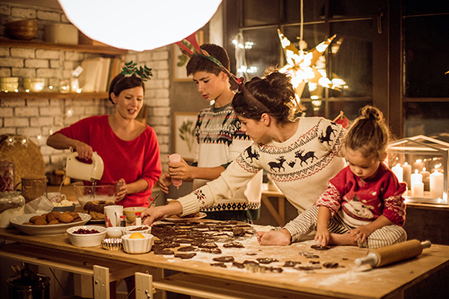 Mother with children in kitchen preparing Christmas cakes